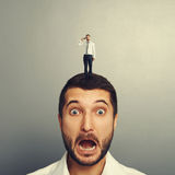Shocked man with small man. On the head Royalty Free Stock Photography
