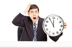 Shocked man in a suit, sitting and holding a clock Royalty Free Stock Photo