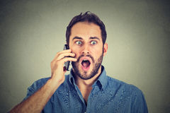 Shocked man talking on mobile phone Royalty Free Stock Photography
