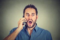 Shocked man talking on mobile phone. Shocked young man talking on mobile phone Royalty Free Stock Photography