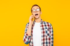 Shocked man talking on the phone, on a yellow background stock photos