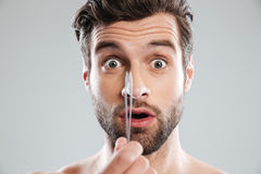 Shocked man with tweezer looked camera Royalty Free Stock Photos
