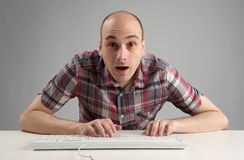 Shocked man using keyboard Stock Photo