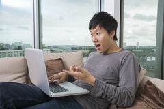 Shocked man using laptop on sofa at home Royalty Free Stock Photos