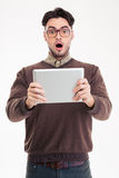 Shocked man using tablet computer. Portrait of a shocked man using tablet computer isolated on a white background Stock Photos