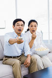 Shocked man and woman at home on couch Royalty Free Stock Photos