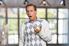 Shocked mature man on blurred background. Amazed middle-aged man gesturing with hand. Surprised face of male person stock photography