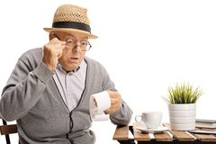 Shocked mature man seated at a coffee table looking at the bill. Isolated on white background Royalty Free Stock Photos