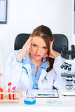 Shocked medical doctor woman sitting at table Stock Photo
