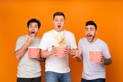 Shocked men eating popcorn and watching scary movie. Over orange background royalty free stock images