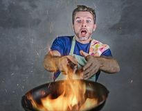 Shocked messy man with apron holding pan in fire burning the food in kitchen disaster and unskilled and unexperienced terrible ho royalty free stock images