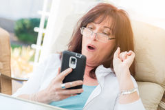 Shocked Middle Aged Woman Gasps While Using Her Smart Phone Stock Photo