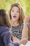 Shocked Mixed Race Girl Talking with Girlfriend Stock Photo