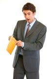 Shocked modern businessman checking parcel Stock Photos