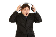 Shocked modern businessman removes headphones Royalty Free Stock Image