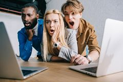 Shocked multicultural business colleagues watching on laptop. Screen royalty free stock images