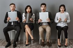 Shocked multicultural business people with folders and notebooks waiting. For job interview royalty free stock images