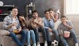 Shocked multiethnic friends watching movie at home royalty free stock photo