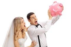 Shocked newlywed couple shaking an empty piggybank royalty free stock photography