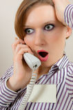 Shocked news. Girl shocked by the news over the phone Royalty Free Stock Photos