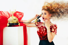 Shocked by news beautiful redhead fashion woman on telephone. Surprised pretty girl talking on telephone in red dress Stock Images