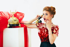 Shocked by news beautiful redhead fashion woman on telephone. Surprised pretty girl talking on telephone in red dress Stock Photo