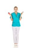 Shocked nurse or female doctor holding stethoscope and heart mod Stock Photo