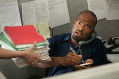Shocked Office Worker. Shocked African-American office worker on a phone call given a stack of files royalty free stock image
