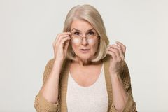 Shocked old woman in disbelief lowering glasses looking at camera royalty free stock image