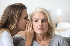 Shocked older woman listening to young friend whispering secret. Shocked older women listening to young female whispering in ear, friend gossiper telling secret royalty free stock images