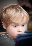Shocked by online content. Concept of a young child that is shocked by what he sees on an online website Stock Image