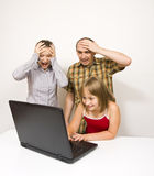 Shocked parents. A cute little girl using a laptop, watching something shocking for the parents - an illustration of danger that threatens the children if they Stock Image