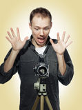 Shocked photographer with retro camera. Young photographer is looking shocked to his medium-format camera Stock Photos