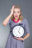 Shocked pinup girl in striped dress holding the clock Stock Photography