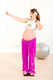 Shocked pregnant standing on weight scale. Shocked pregnant woman standing on weight scale and holding measure tape in hand stock image