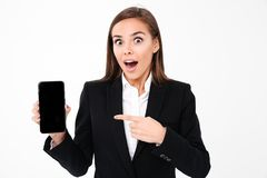 Shocked pretty businesswoman showing display of mobile phone Royalty Free Stock Photography