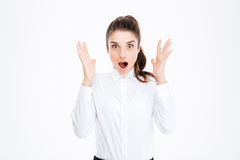 Shocked pretty young businesswoman with raised hands. Over white background Royalty Free Stock Photo