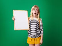 Shocked pupil showing blank board against green background Royalty Free Stock Photos