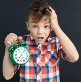 Shocked pupil with big green alarm clock - back to school concept royalty free stock images
