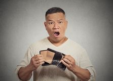 Shocked puzzled business man worker employee holding empty wallet royalty free stock photo
