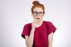 Shocked woman in glasses looking at camera with open mouth and touching head. Shocked redhead woman in glasses and red shirt looking at camera with open mouth Stock Photos