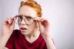 Shocked woman looking at camera with open mouth and touching glasses. Shocked redhead woman wearing red shirt looking at camera with open mouth and touching Royalty Free Stock Image