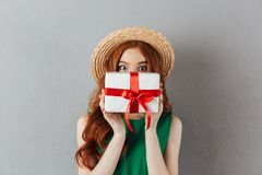 Shocked redhead young woman covering face with present. Image of shocked redhead young woman in green dress and hat standing over grey wall background. Looking Royalty Free Stock Photo