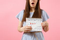 Shocked sad woman in blue dress, hat holding sanitary napkin, female periods calendar for checking menstruation days stock image