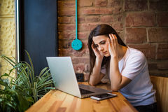 Shocked and sad woman holding computer, laptop tablet screen looking surprised in coffee shop Stock Photos