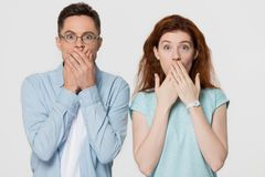 Shocked scared couple covering mouth with hands looking at camera. Shocked scared amazed couple covering mouth with hands feel horrified stunned looking at royalty free stock photo