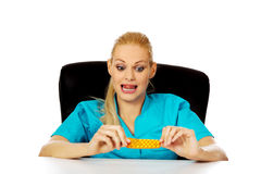 Shocked and scared female nurse or doctor sitting behind the desk and holding packet of pills Royalty Free Stock Photos