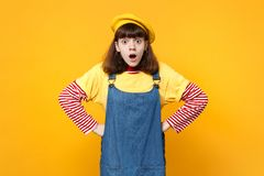 Shocked scared girl teenager in french beret, denim sundress keeping mouth open standing with arms akimbo isolated on. Yellow background. People sincere royalty free stock photography