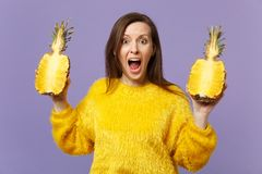 Shocked scared screaming young woman in fur sweater holding halfs of fresh ripe pineapple fruit  on violet royalty free stock image