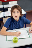 Shocked Schoolboy With Cheat Sheet Sitting At Desk Stock Photos